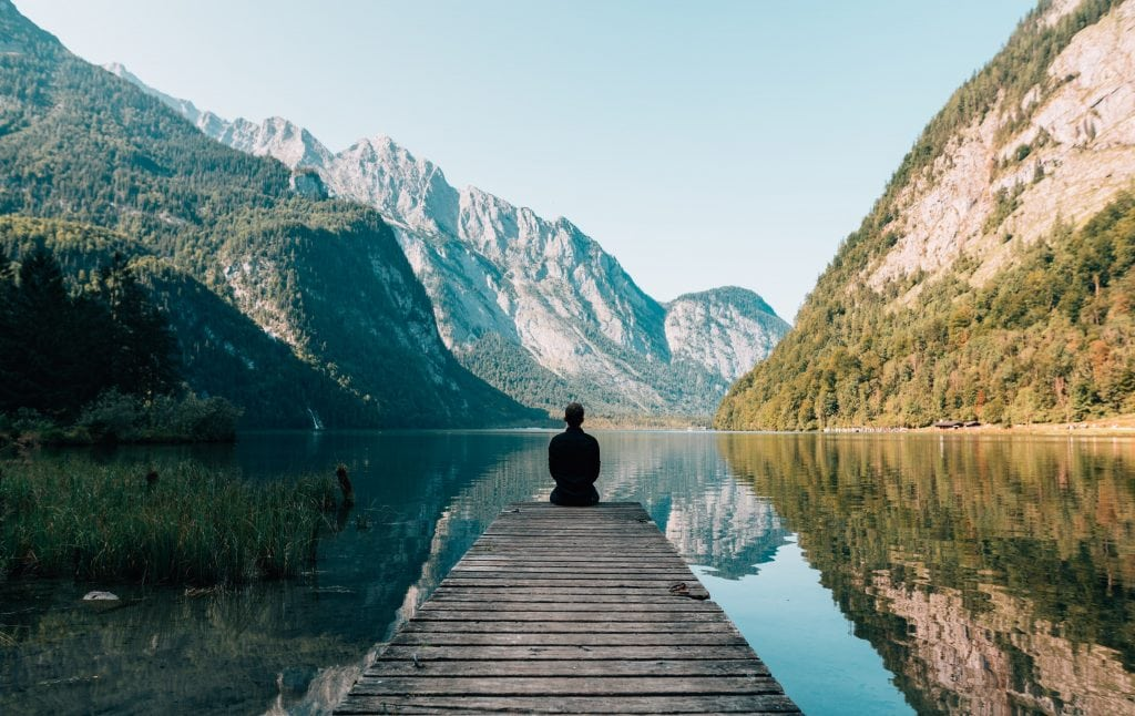 Man sitting near lake and mountains. 15 uplifting thoughts to help you have inner peace